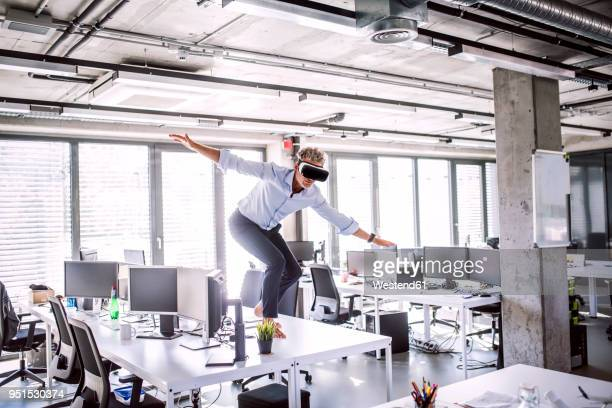 Barefoot mature businessman on desk in office wearing VR glasses