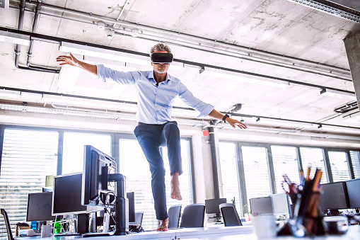 Barefoot mature businessman on desk in office wearing VR glasses - gettyimageskorea