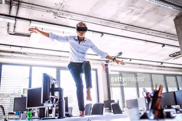barefoot mature businessman on desk in office wearing vr glasses - beweglichkeit stock-fotos und bilder