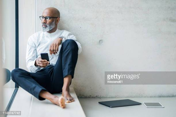 barefoot mature businessman with smartphone sitting on window sill looking at distance - barefoot black men stock pictures, royalty-free photos & images