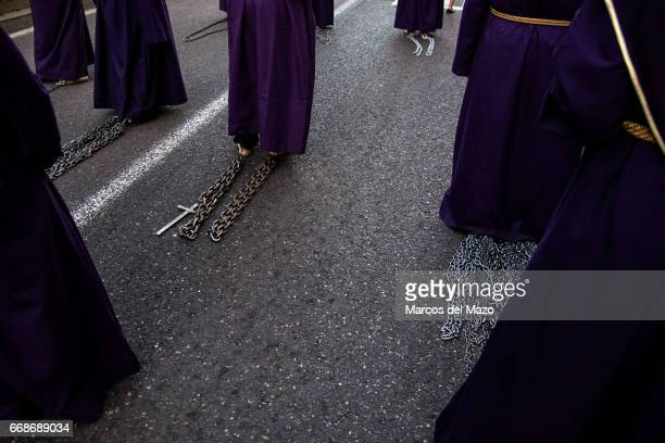 Barefoot penitents of the brotherhood of Jesus de Medinaceli drag chains and crosses tied to their ankles during the procession of Good Friday