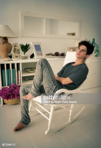 barefoot teen male model sitting on a rocking chair - barefoot men stock photos and pictures