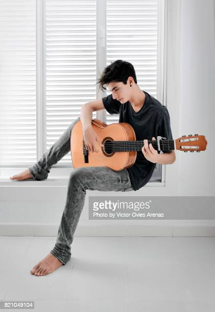 barefoot teen male playing guitar sitting on a window frame - mens bare feet stock photos and pictures