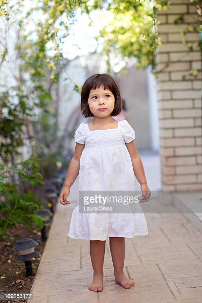 Barefoot toddler In a white dress