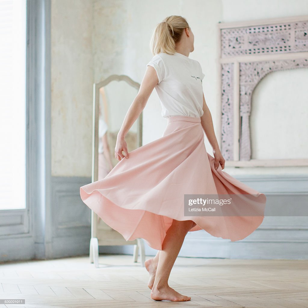 Barefoot woman dancing in front of a mirror : Stock Photo