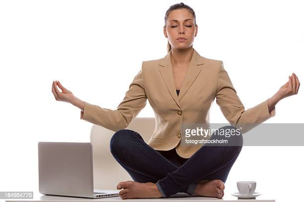 Barefoot woman in business attire meditating