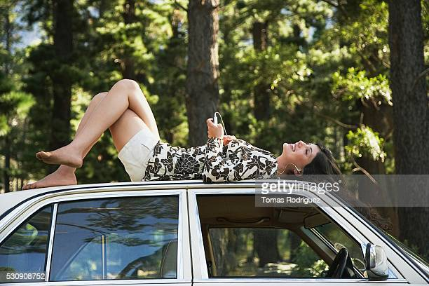 Barefoot woman lying on top of car