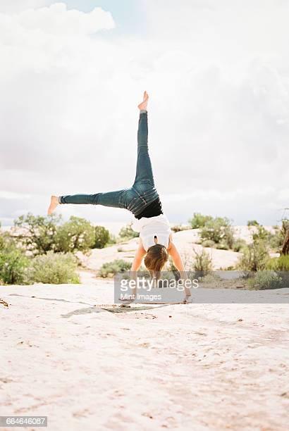 Barefoot woman wearing jeans, cartwheeling