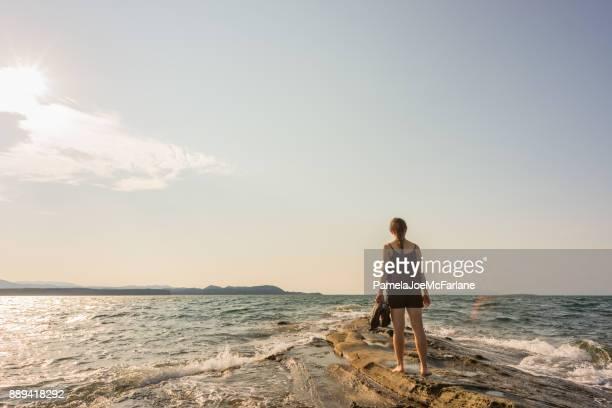 Mujer joven descalza en península mirando hacia fuera en el océano abierto