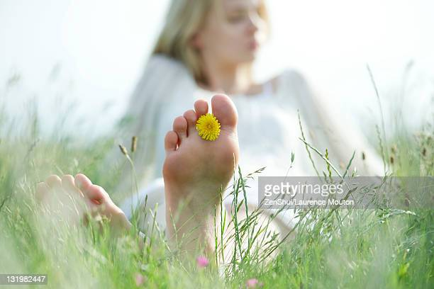 Barefoot young woman sitting in grass with dandelion flower between toes, cropped