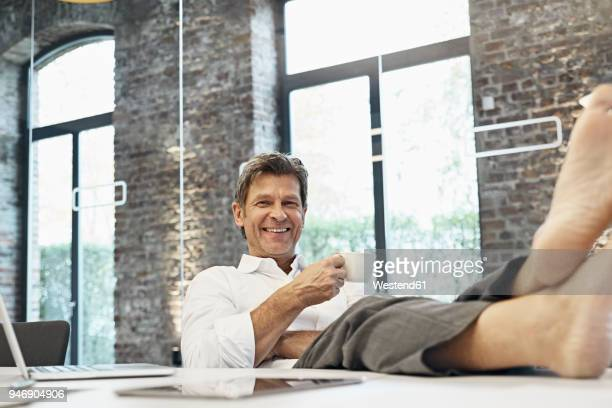 Barefooted businessman relaxing and drinking coffee in modern office
