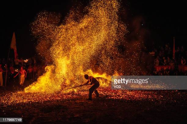 A barefooted man walks through burning charcoal as he performs 'Lianhuo' or 'fire walking' to celebrate the Double Ninth Festival on October 7 2019...