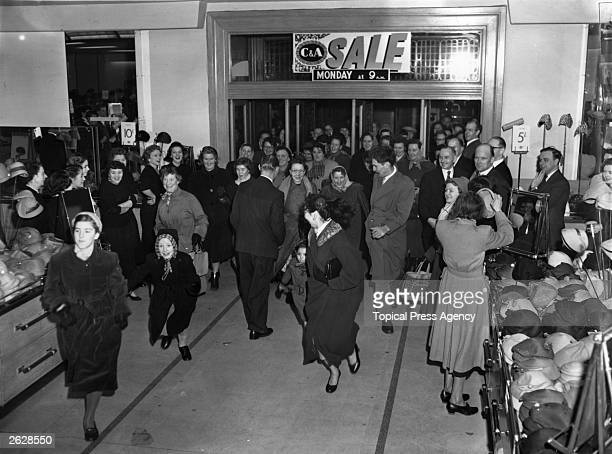 Bargain hunters swarm in as the doors are opened at the beginning of the Modes Sale at C A department store at Marble Arch Oxford Street London