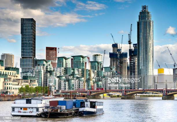barge and ferries moored in the thames in front of vauxhall bridge and the modern apartment blocks of st george wharf and tower in london - flat stock pictures, royalty-free photos & images