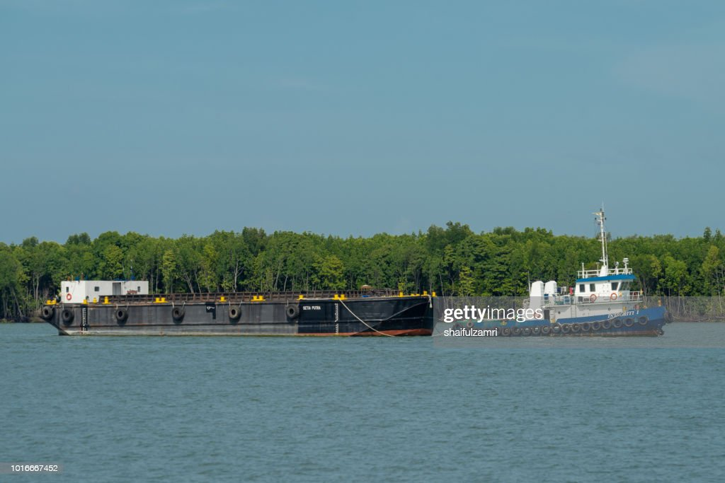Barge and tug boat cargo ship in Port Klang river. : Stock Photo