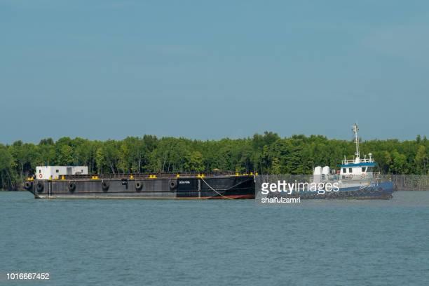 Barge and tug boat cargo ship in Port Klang river.