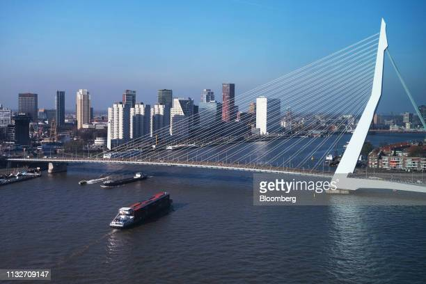 A barge carries shipping containers as the Erasmus Bridge spans the Nieuwe Maas river in Rotterdam Netherlands on Friday March 22 2019 UK Prime...