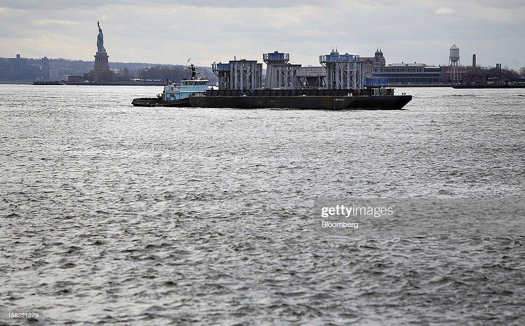A barge delivers the spire of One World Trade Center as the Statue of Liberty stands in the background, in New York, U.S., on Tuesday, Dec. 11, 2012. The crowning spire, split into nine pieces weighing 70 tons each, was brought across New York Harbor from New Jersey's Port Newark today. Photographer: Victor J. Blue/Bloomberg via Getty Images