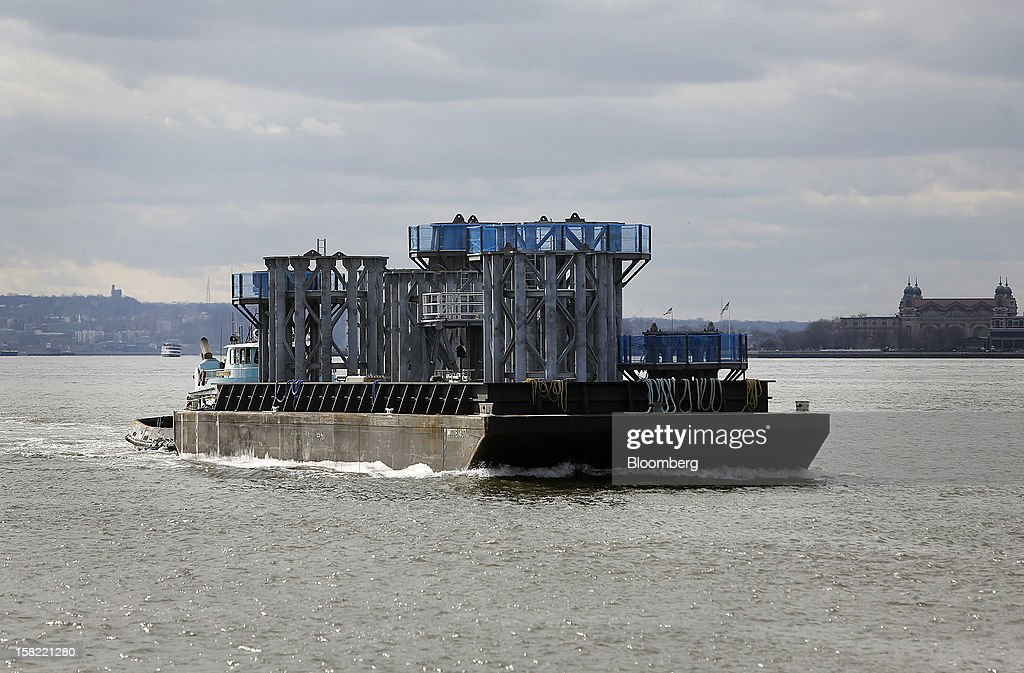 A barge delivers the spire of One World Trade Center in New York, U.S., on Tuesday, Dec. 11, 2012. The crowning spire, split into nine pieces weighing 70 tons each, was brought across New York Harbor from New Jersey's Port Newark today. Photographer: Victor J. Blue/Bloomberg via Getty Images
