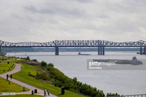 A barge moves along the Mississippi River towards the MemphisArkansas bridge Frisco Bridge and Harahan Bridge past Tom Lee Park in Memphis Tennessee...