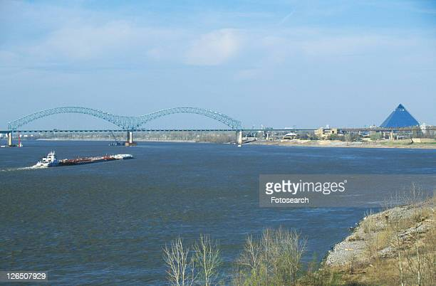 barge on mississippi river with bridge and memphis - memphis bridge stock photos and pictures