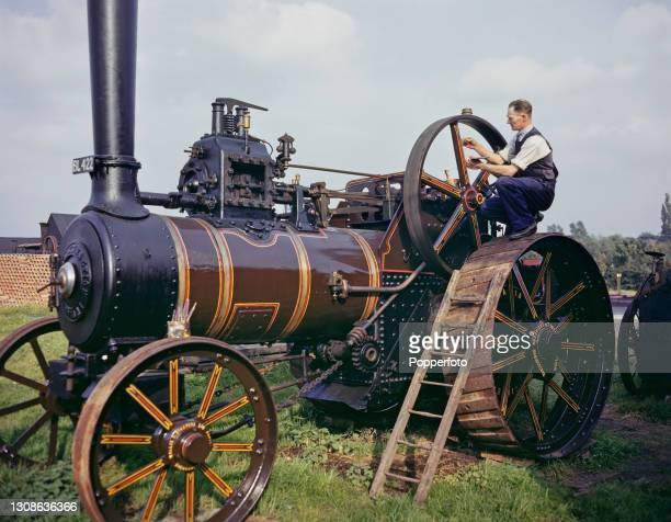 Barge painter and sign writer Frank Jones decorates a traction engine with paints in England in October 1945.