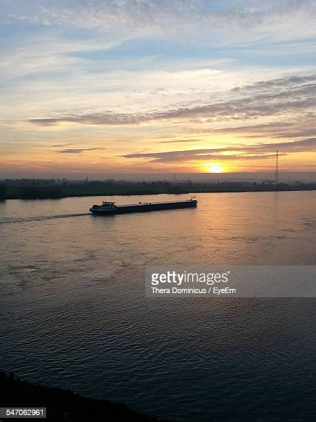 barge sailing on sea against sky at sunset - barge stock photos and pictures