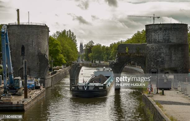 "Barge sails under the ""Pont des Trous"" medieval bridge as it is being demolished in Tournai, where the Scheldt river will be enlarged to allow larger..."