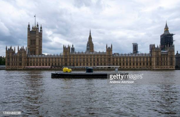 Barge sits moored up in the river Thames outside the The Palace of Westminster, also known as the Houses of Parliament or the House of Commons on the...
