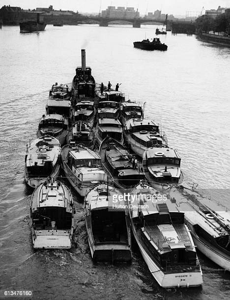 A barge tows several small boats up the Thames for repairs after they were used in the emergency evacuation of French and British troops at Dunkirk...