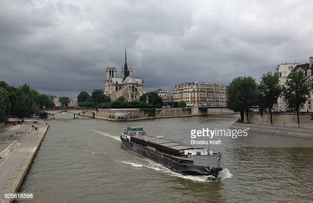 A barge travels down the Seine River in front of Notre Dame in Paris