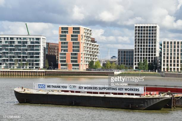 Barge with a sign thanking NHS staff is seen working on the River Thames in London on May 14, 2020. - Britain's economy shrank in the first quarter...