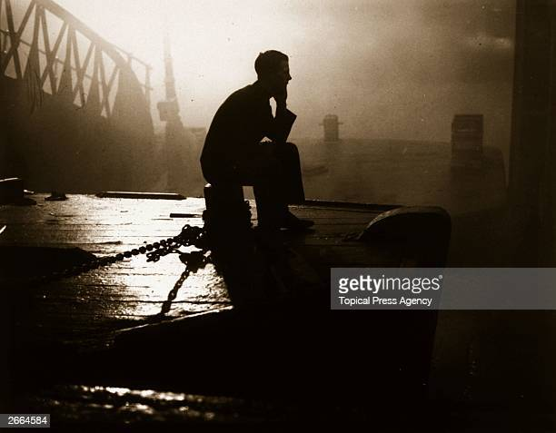 Bargee sitting on the stern of his barge waiting for the London fog to lift before he can start work.
