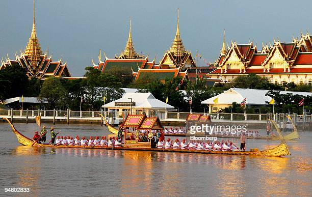 Barges drift past the Royal Grand Palace in Bangkok during a barge procession with more than 2000 oarsmen on 52 barges on the Chao Phraya river on...