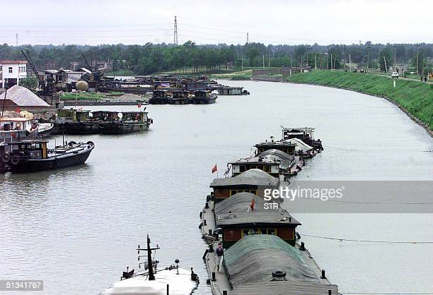 Barges make their way along the ancient canal near the eastern Chinese city of Nanjing 02 August 2002 China plans to dig a 322kilometer canal to...