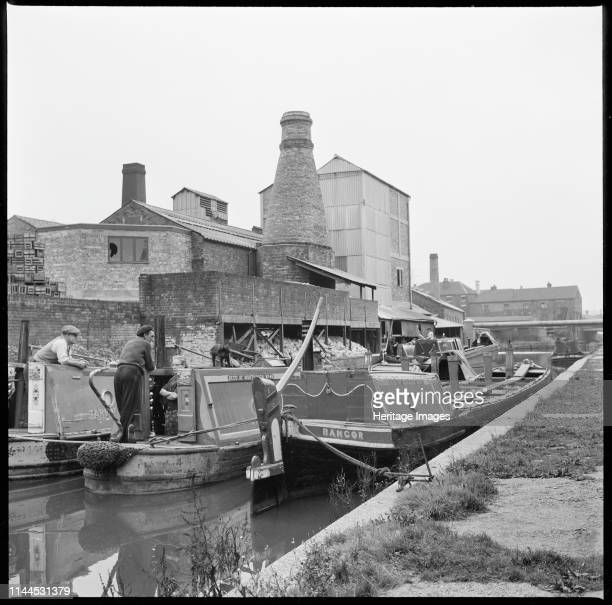 Barges on the Trent & Mersey Canal, Stoke-on-Trent, 1965-1968. A group of barges beside W J Dolby's flint calcinating kiln. Artist Eileen Deste.