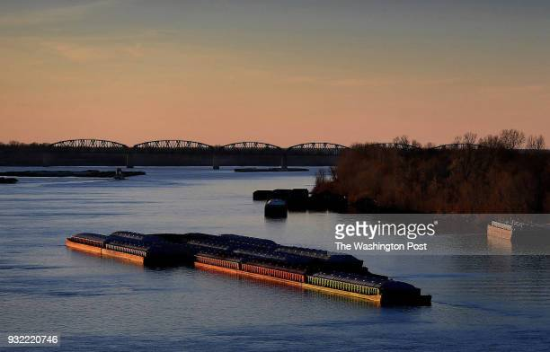 Barges on the water at the confluence of the Mississippi and the Ohio Rivers Photo taken from the Cairo Mississippi River bridge that was built in...
