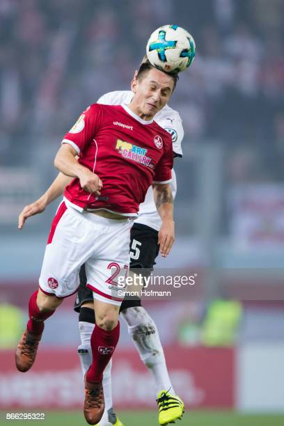 Baris Atik of Kaiserslautern jumps for a header with Tim Baumgartl of Stuttgart during the DFB Cup match between 1 FC Kaiserslautern and VfB...