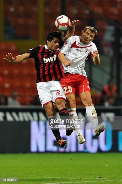 Bari's Bielorussian forward Vitali Kutuzov jumps for the ball with A.C. Milan's midfielder Gennaro Ivan Gattuso during their Serie A football match...
