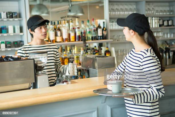 Barista and waitress in coffee shop
