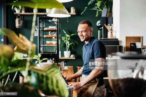 barista at work behind counter in cafe - polo shirt stock pictures, royalty-free photos & images