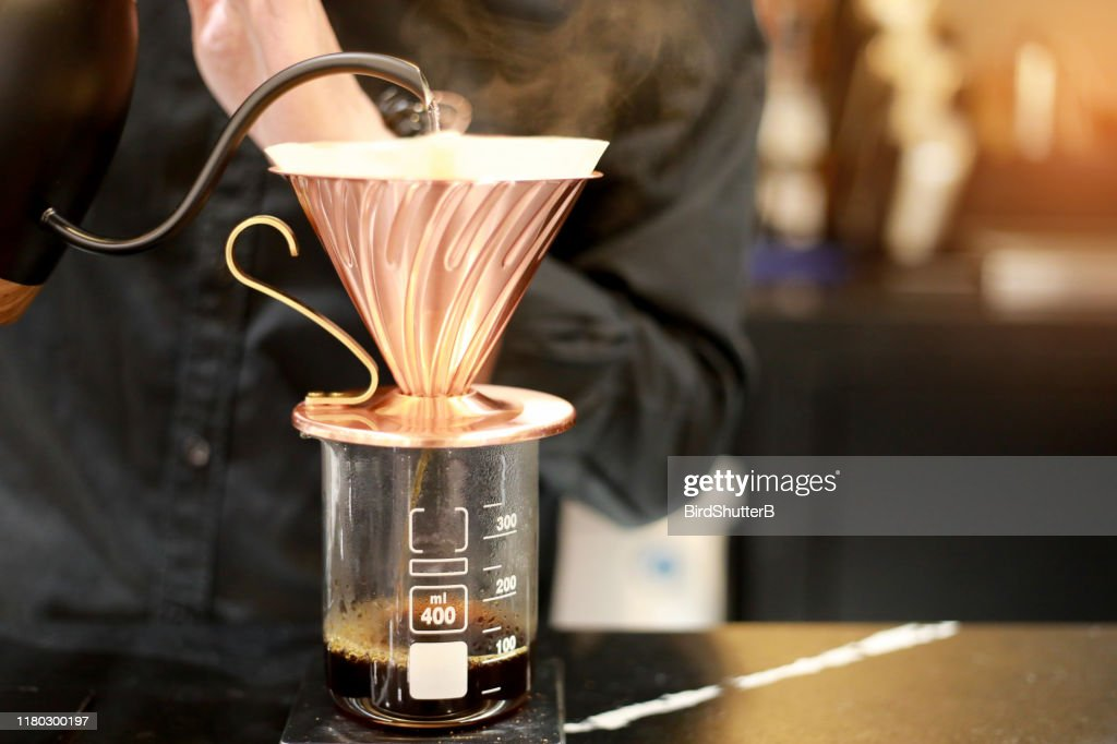 Barista brewing drip coffee with hot water pot with smoke and hand. Drink concept. Dark tone. : Stock Photo