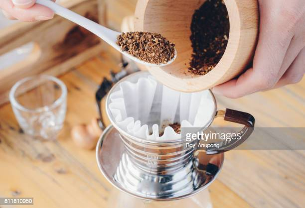 Barista bring the coffee ground powder to the paper filter before brew coffee.
