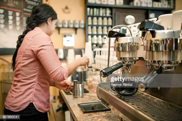 Barista busy with espresso machine in cafe