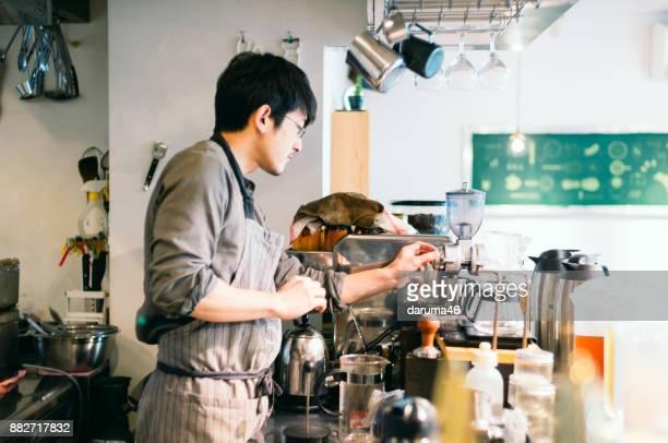 バリスタ カフェ カウンターでコーヒー マシンを片付け