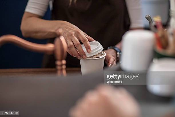 Barista closing lid of disposable coffee cup