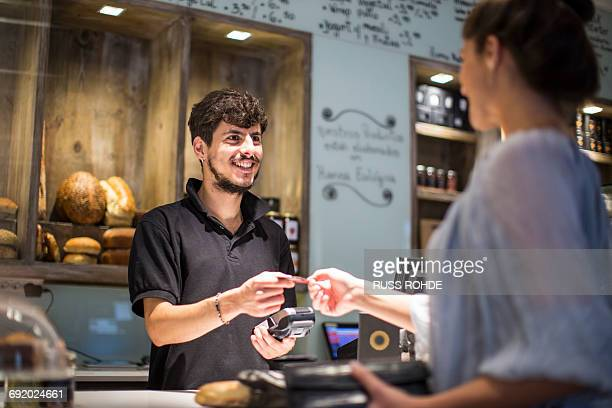 Barista handing credit card to female customer at cafe counter