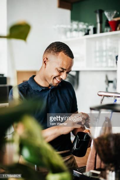 barista heating up some milk while making coffee - hoch position stock-fotos und bilder