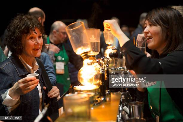 Barista Hiromi Buchanan right brews siphon coffee for Pat Sollars of Fircrest Washington at the Annual Meeting of Shareholders in Seattle Washington...
