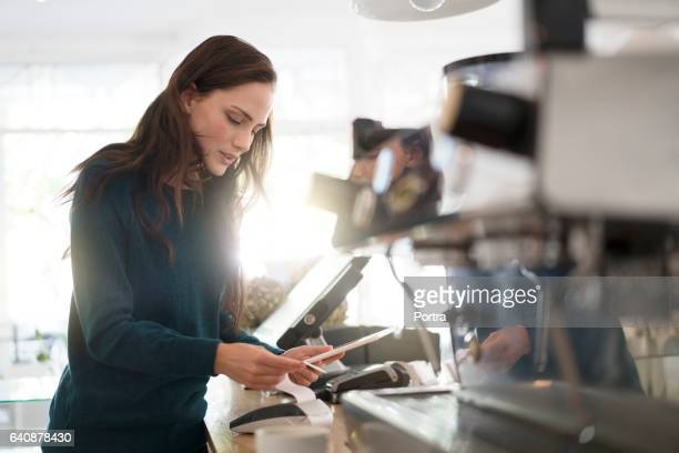 Barista holding digital tablet and bill in cafe